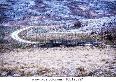 A bridge in the middle of remote countryside in Iceland during winter shows the grassy terrain mingled with ice and snow.