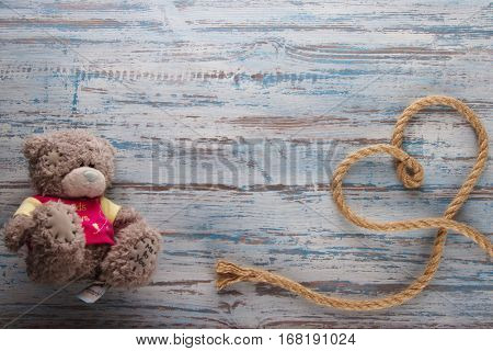 rope heart on a Teddy bear lying on wooden blue background color