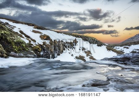 A cold snowy river in the highlands of Iceland framed by pastel skies and rugged terrain offers scenic landscape epitomizing the frozen wilderness.