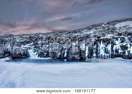 A frozen river in the highlands of Iceland framed by dark pastel skies and rugged terrain offers scenic landscape epitomizing the frozen wilderness.