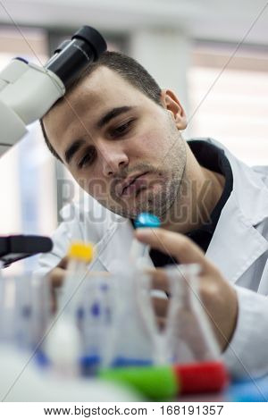 Young doctor performs tests and lab wearing a white coat