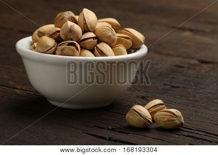 Group of pistachios in a bowl over a wooden background