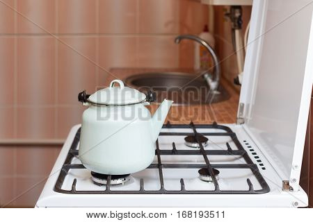 Blue kettle made of steal standing on kitchen gas stove