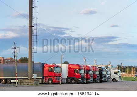 Narva, Estonia - August 20, 2016: Heavy trucks with trailers loaded with merchandise stand in a row on an asphalt car platform. International cargo transportation and logistics. Road transport infrastructure inevening at sunset industrial landscape
