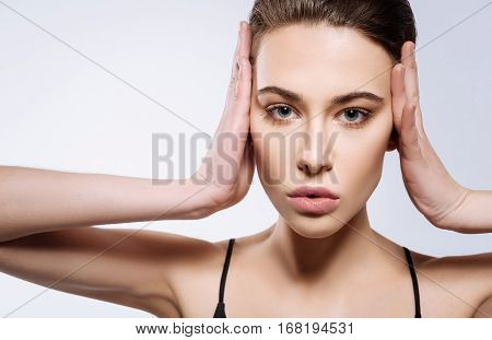 Attracting attention. Bewitching blue-eyed professional model accentuating her face by holding it in her hands and standing isolated on white background
