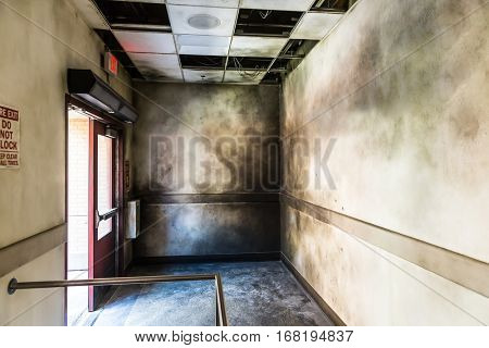 Gloomy burned hall and opened fire exit.
