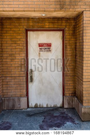 Grunge brick wall and door with no entry sign.