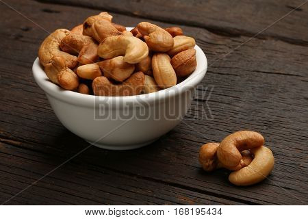 Group of cashew nuts in a bowl over a wooden background
