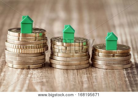 Real estate mortgage concept with small green houses on top of stacked coins
