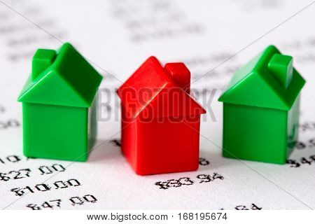 Green and red houses on a financial report background