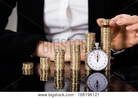 Businesswoman Stacking Coins With Stopwatch In Front On Desk. Quick Money Concept