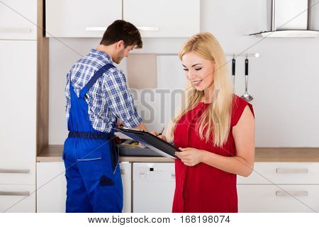 Smiling Housewife Woman Signing Appliance Repair Invoice From Male Plumber In Kitchen
