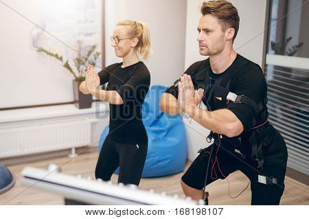 Sportsman In Ems Suit And His Personal Trainer In Yoga Pose