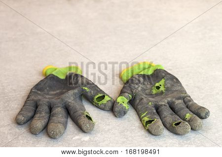 Used old dirty torn worker's gloves as a metaphor concept or symbol for the end of the work season