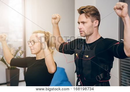 Serious Sportsman Working Out With Personal Coach At Gym