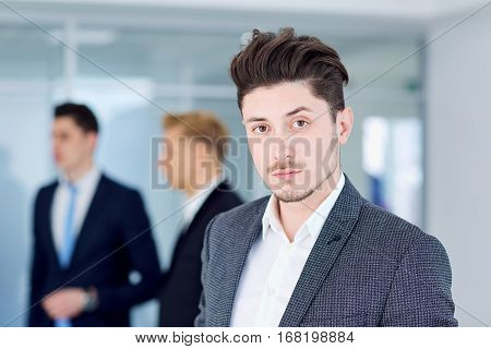 Young businessman  on the background of his business partners.