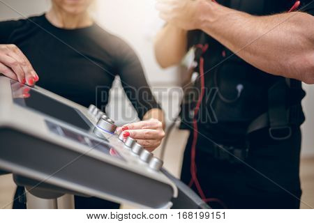 Trainer Hands Turning On Ems Device