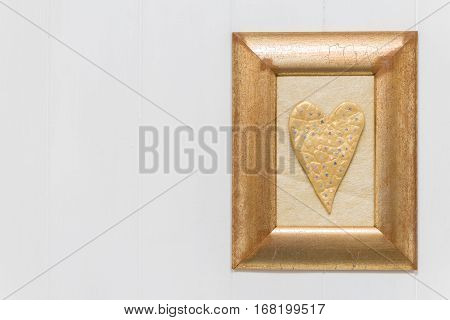 Gold Heart In Frame On White Wooden Background. Copy Space.