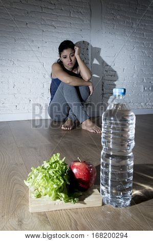 young woman or teenager girl sitting on ground alone and worried at home suffering nutrition and eating disorder in diet and weight loss obsession with healthy food in anorexia and bulimia concept