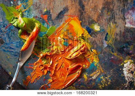 Create it. Top view of a putty knife and orange and green paints lying on a palette.