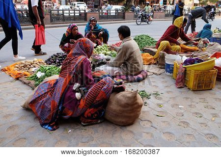 JAIPUR, INDIA - FEBRUARY 16: Indian women in brightly colored saris buying fruit and vegetables by the side of the road in Jaipur, Rajasthan, India on February 16, 2016.
