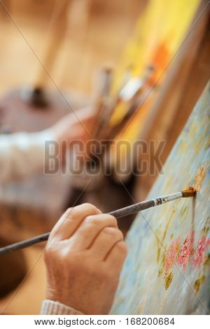 Process of creating. Close up of artists hand painting on a canvas and using brush while working.