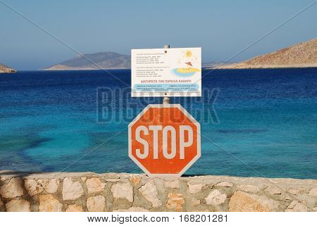 HALKI, GREECE - JULY 16, 2016: A stop sign and sunbed price list at Ftenagia beach in Emborio on the Greek island of Halki. Tourism and fishing are the two main industries of the Dodecanese island.