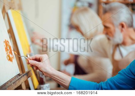 Productive cooperation. Concentrated artists working together in painting studio while holding brushes and enjoying their hobby.