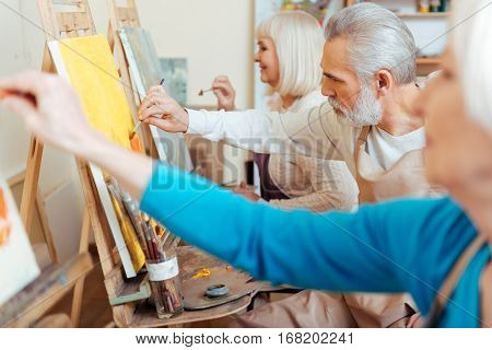 Best cooperation. Three concentrated professional elderly artists spending time in painting studio while painting and enjoying their hobby.