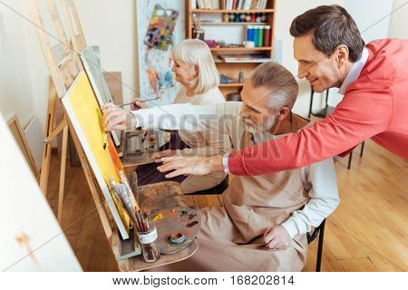 Perfect advice. Overjoyed professional artist helping elderly man while spending time in painting studio and drawing a picture.