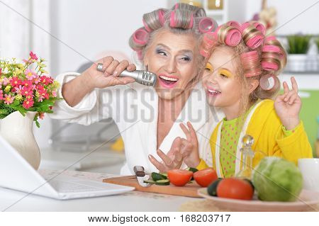 grandmother with granddaughter at home singing songs
