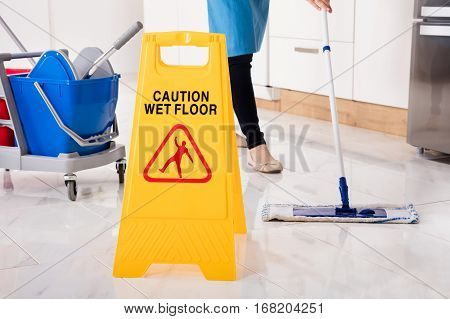 Close-up Of Yellow Wet Caution Sign On Wet Floor In Kitchen