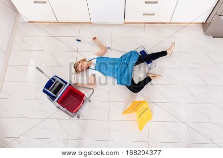 High Angle View Of Young Fainted Housemaid Lying After Accident On Floor In Kitchen