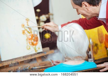 Nice learner. Talented young concentrated artist teaching elderly woman while drawing and spending time in painting school.