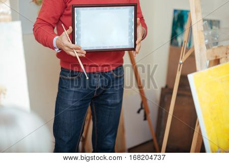 Finally graduated. Close up of young handsome man demonstrating a painters diploma being given to him after finishing painting school.