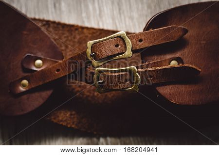 brown leather belts in a wooden background