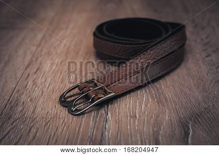 leather brown belts in a wooden background
