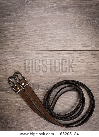leather brown belt  in a wooden background