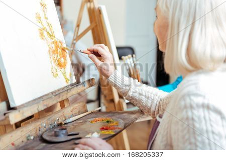 Do your best. Creative woman painting and using palette while spending time in painting studio