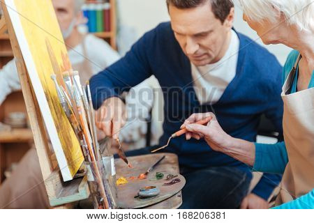 Perfect advisor. Delighted handsome young artist helping elderly woman while she painting and spending time in painting studio.