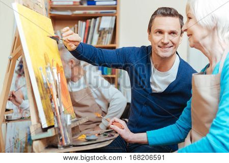 poster of Friendly teacher. Overjoyed handsome young artist helping elderly woman while he painting and spending time in painting studio