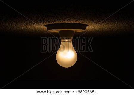 Photo of a lit light bulb with darkness around.