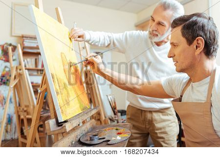 Make it beautiful. Inspired elderly professional artist painting while working with his young colleague and spending time in painting studio.