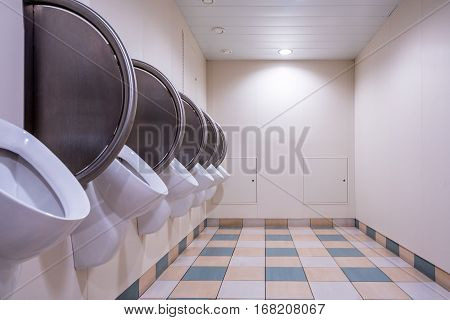 Men's public restroom with urinals on the wall and checkered floor. Perspective of empty room, horizontal.