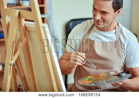 Well equipped. Concentrated handsome young artist holding a brush and palette while painting and sitting in painting studio.