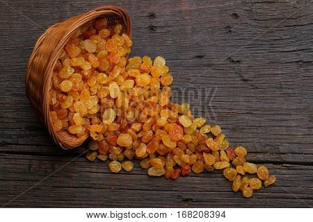 Group of raisins in a bowl over a wooden background