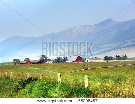 Absaroka Mountains serve as backdrop for this quiet farm in Happy Valley Montana. Pasture is being irrigated and is surrounded by rustic fence.