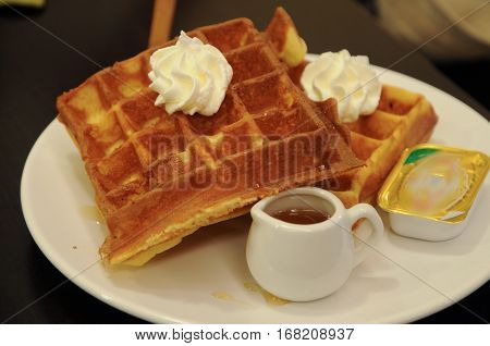 Plate Of Belgium Waffles With Butter, Cream And Syrup