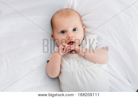 Portrait On An Innocent Child On White Blanket
