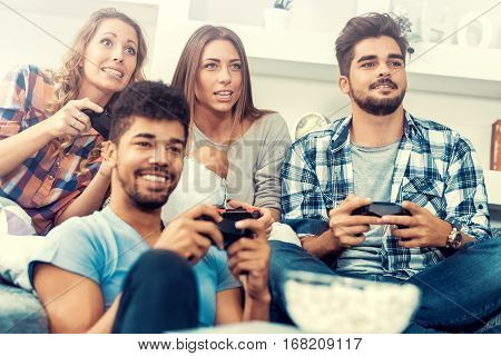 Young friends playing video games at home.
